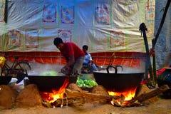 Qualche gente sta cucinando l'alimento in una grande casseruola per la celebrazione della cerimonia di nozze immagini stock libere da diritti