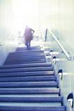Qualcuno cammina sulle scale all'indicatore luminoso Immagine Stock