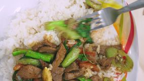 Qualcuno mangia con una forcella, riso con fegato, alimento di vista superiore su un piatto bianco stock footage