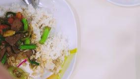 Qualcuno mangia con una forcella, riso con fegato, alimento di vista superiore su un piatto bianco video d archivio