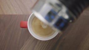 Qualcuno mano aggiunge il latte alla tazza rossa con caffè disposto sulla tavola di legno video d archivio