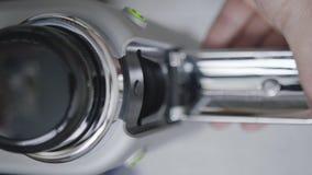 Qualcuno mano apre la scanalatura della capsula della macchina automatica grigia compatta del caffè stock footage
