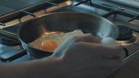 Qualcuno olio di versamento in pentola e di rottura uova là, poi essi che friggono archivi video