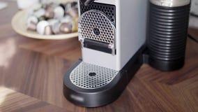 Qualcuno passa a posti la tazza rossa sul vassoio di piccola macchina del caffè con le capsule stock footage