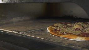 Qualcuno prende la pizza dal forno con la pala speciale video d archivio
