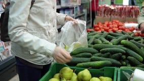 Qualcuno sceglie le pere nel supermercato stock footage
