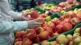 Qualcuno seleziona le mele nel supermercato video d archivio