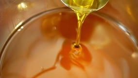 Qualidade orgânica do óleo do canola da colza bio, bolhas ativas, misturando e derramando em um tambor de aço, para o alimento fr video estoque