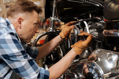Qualified able professional drawing up a bolt tight. Take it seriously. Trained clever local mechanic using special instruments for fixing his bike and keeping Stock Image