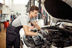A qualified automechanic is searching for bugs at a car repair service stock image