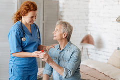 Qualified capable doctor assisting feeble man at home. Thank you for helping me. Delicate trained professional women taking care of elderly gentleman while royalty free stock photos