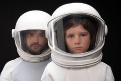 Qualified cosmonauts are expressing thoughtfulness. Professional team. Portrait of serious two spacemen are standing together wearing helmet and protective Royalty Free Stock Photography