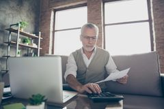 Qualified experienced intelligent confident concentrated old man. Qualified experienced intelligent confident concentrated old bearded man checking his royalty free stock image
