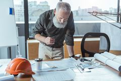 Professional old man is working in office with specialized equipments. Qualified gray-haired engineer with beard is leaning over table and holding glasses while Royalty Free Stock Image
