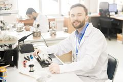 Qualified lab technician analyzing manometer in workshop. Cheerful confident bearded male repairing engineer in lab coat sitting at table with tools and Stock Photo