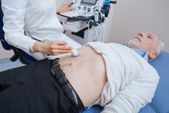 Qualified practitioner providing ultrasonic abdomen monitoring at work Stock Photos