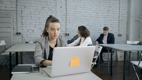 Adult woman using personal computer and sitting in office. Qualified, professional businessperson working indoor workspace with modern interior office. Adult stock footage