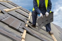 Workman install tile on roof of new house under construction stock images