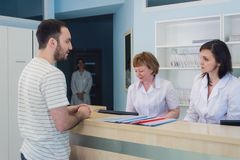 Qualified smiling doctors working with client at reception desk in hospital stock photo