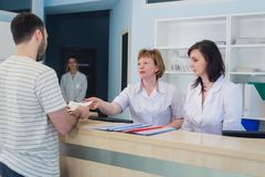 Qualified smiling doctors working with client at reception desk in hospital royalty free stock images