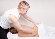 A qualified therapist doing  massage Stock Images
