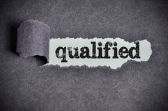 Qualified word under torn black sugar paper Stock Photos