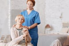 Qualifizierte private Krankenschwester, die älteren Patienten unterstützt lizenzfreies stockbild