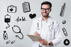 Qualifizierter lächelnder Doktor beim Schreiben seinem Patienten einer Verordnung Stockfotos