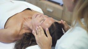 Qualifizierter Massagemeister, der Face lifting im Badekurortsalon macht stock video