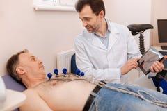 Qualifizierter mitfühlender Doktor, der Diagnose seinem Patienten erklärt lizenzfreies stockfoto