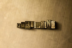 QUALIFYING - close-up of grungy vintage typeset word on metal backdrop Royalty Free Stock Image