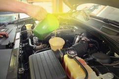 Qualità di rifornimento di carburante e di versamento dell'olio nell'automobile del motore fotografia stock