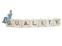 Quality. A quality manager sitting on the word quality royalty free stock photos