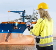 Quality assurance manager inspecting a dredging vessel. Female quality assurance manager takinga picture of a dredging vessel with her tablet, looking for Stock Photo
