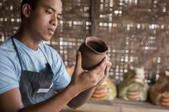 Quality check of pottery product. Male potter checking vase in pottery workshop Royalty Free Stock Images