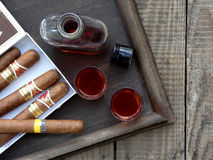 Quality cigars and cognac. On an old wooden table stock image