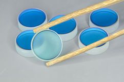 Quality control. Closeup of optical mirrors batch with focus on selected one by wooden tweezers Stock Image