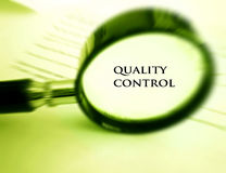 Quality control concept. A conceptual photograph of the words quality control, focused by a magnifying glass. Horizontal concept image, nobody in picture Stock Images