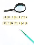 Quality control concept. A conceptual still life photograph of the words quality control spelt out in block letters, taken on white background with magnifying Stock Image