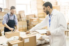 Quality Control at Factory Warehouse. Profile view of bearded Arabian inspector wearing lab coat holding clipboard in hand while carrying out quality control at Royalty Free Stock Image