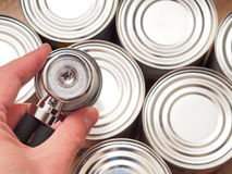 Quality control. Hand with stethoscope hovering over some cans, focus is on the stethoscope - for concepts like quality control, food safety or business audits Stock Photo