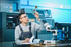 Quality control part. Metal worker machine male Royalty Free Stock Photography
