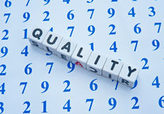 Quality counts. Text ' quality ' in black uppercase letters on white cubes placed upon an array of blue numbers making the concept ' quality counts Royalty Free Stock Images