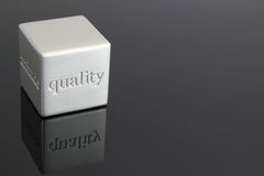 Quality cube. Metallic cube paperweight with the word quality etched in the side Stock Images