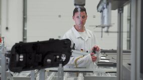 Quality engineer programs a machine for 3D measurement of plastic casting in the automotive industry
