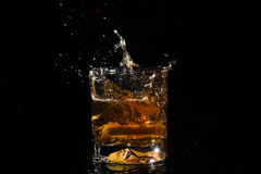 Quality glass of whiskey with splashes from falling slice of lemon. Royalty Free Stock Photos
