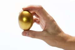 Quality. Holding a golden egg with the hand on a white background, as a concept of quality Royalty Free Stock Images