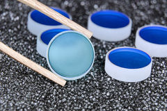 Quality inspection. Closeup of optical mirrors batch with focus on selected one by wooden tweezers Royalty Free Stock Photos