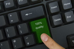 Quality key. Close up of the finger on the green 100 % quality key of the keyboard Royalty Free Stock Image