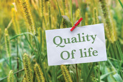 Quality of Life. Concept white note and clipper on a grass field Royalty Free Stock Image